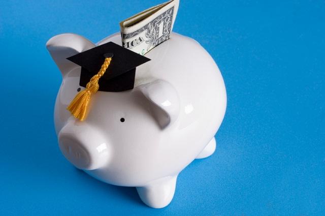 Piggy bank with a graduation cap with dollar bill